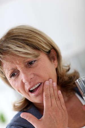 dolor  de diente: Primer plano de mujer mayor que tiene el dolor de muelas