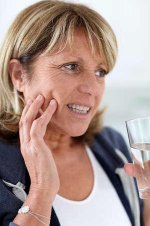 dolor de muelas: Primer plano de mujer mayor que tiene el dolor de muelas