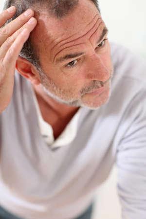 calvitie: Senior homme regarde ses cheveux dans le miroir Banque d'images