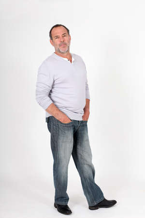 50 years old man: Senior man standing on white background with hands in pocket