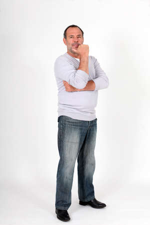 man in jeans: Senior man standing on white background with hand on chin