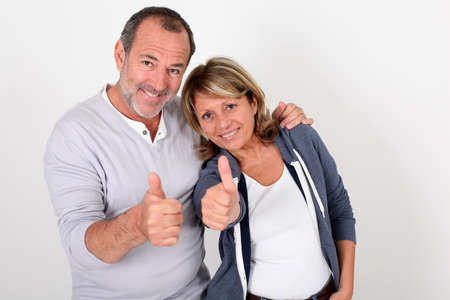 Portrait of senior couple showing thumbs up photo