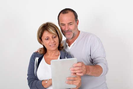 old man beard: Senior couple having fun with electronic tablet Stock Photo