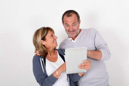 Senior couple having fun with electronic tablet photo