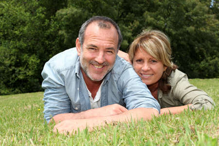 Senior couple having fun laying in grass photo