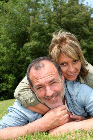 Senior couple having fun laying in grass Stock Photo - 14024658