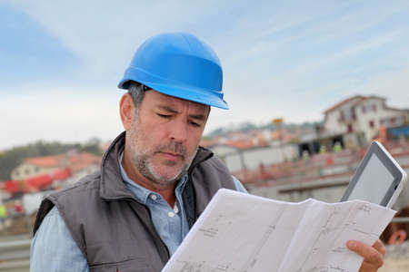 Construction manager controlling building site with plan photo