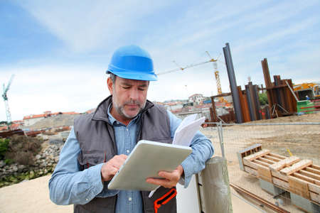 building site: Construction manager controlling building site with plan