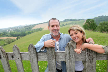 pasture fence: Senior couple leaning on fence in countryside