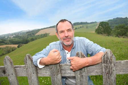 breeder: Portrait of smiling farmer leaning on fence