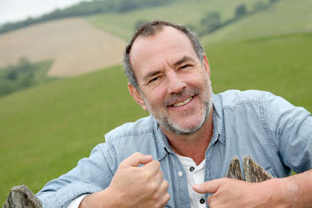 Portrait of smiling farmer leaning on fence photo