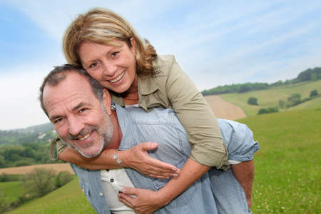Senior man giving piggyback ride to wife photo