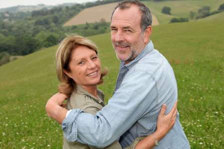 Portrait of happy senior couple in countryside photo