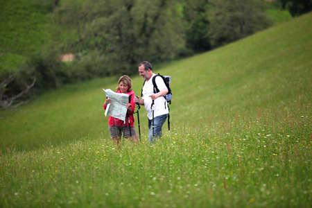 bonne aventure: Randonneurs hauts de lecture carte dans le champ pays