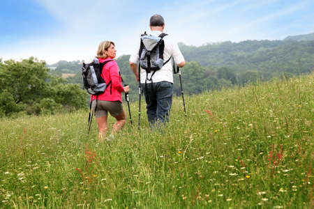 guy with walking stick: Back view of senior couple hiking in countryside