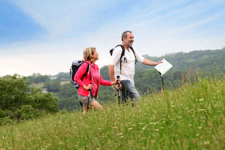 Senior couple hiking in natural landscape photo