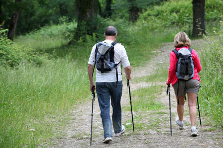 guy with walking stick: Back view of senior couple hiking in forest pathway