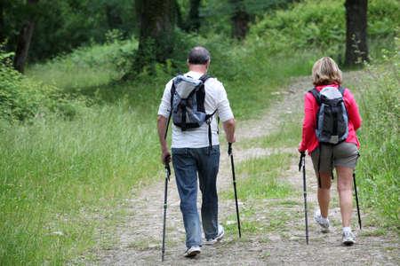 bonne aventure: Vue arrière de la randonnée couple de personnes âgées dans la voie de la forêt Banque d'images