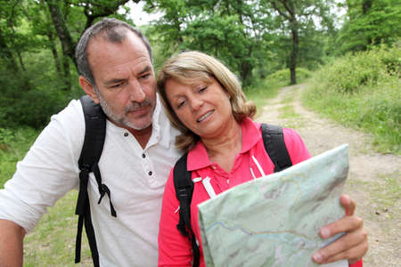 rambling: Senior couple rambling in forest with map