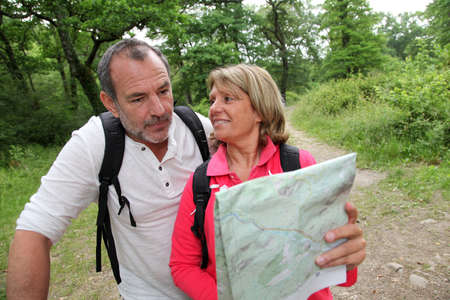 Senior couple rambling in forest with map photo