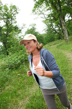 Senior woman jogging in forest photo