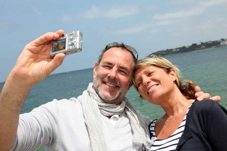Retired couple taking picture of themselves by the sea photo