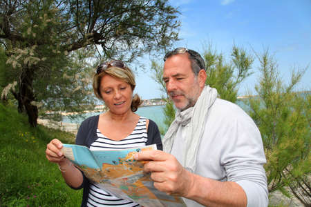 Senior couple on vacation looking at city map photo