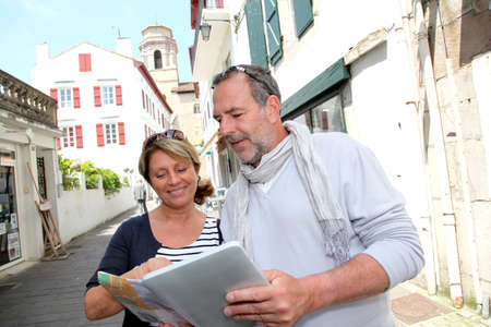 Mature couple in seaside resort looking at map photo