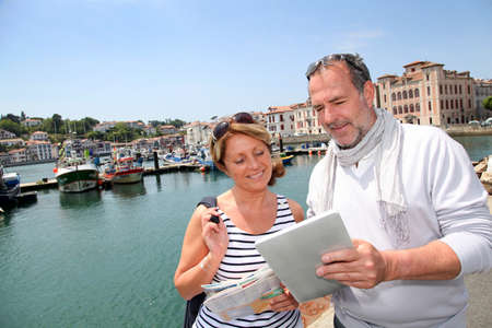 Senior couple using digital tablet to find city tour photo