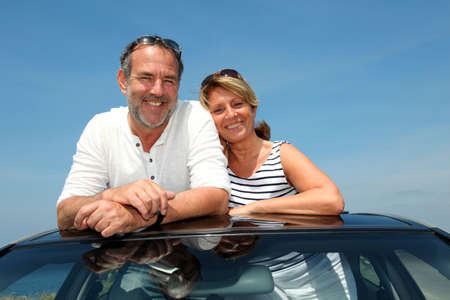 Senior couple in convertible car enjoying day trip photo