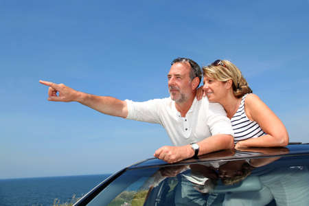 Senior couple in convertible car enjoying day trip
