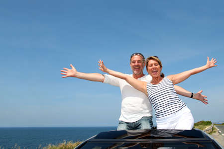 Senior couple en voiture d�capotable en profitant excursion d'une journ�e photo