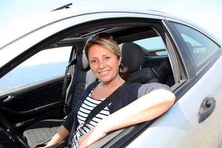 Portrait of senior woman driving car photo