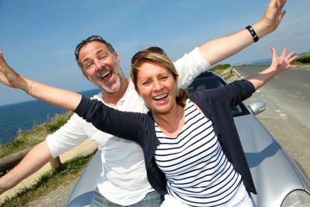 Senior couple in convertible car enjoying day trip photo