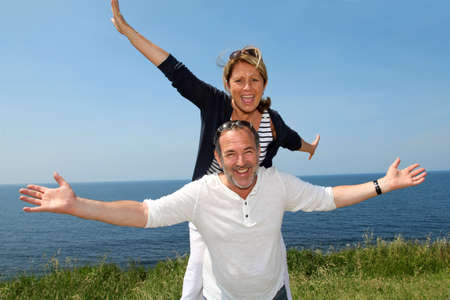 Cheerful couple stretching arms in front of the sea photo
