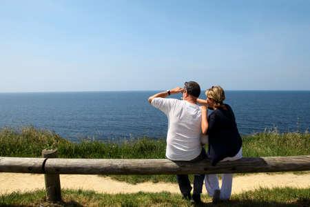sitting area: Couple sitting on fence enjoying panoramic sea view Stock Photo