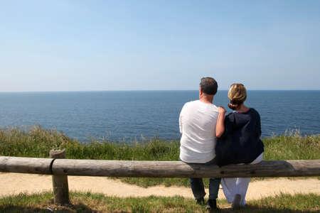 back views: Couple sitting on fence enjoying panoramic sea view Stock Photo