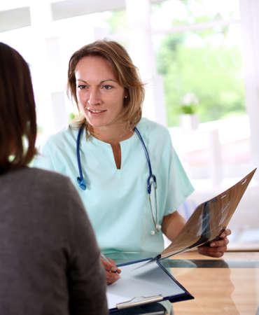 Nurse with patient in check-up room photo