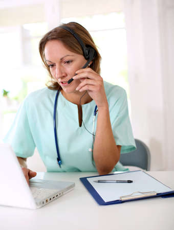 helpdesk: Nurse in front of laptop with headset