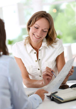 Woman architect presenting plan to client photo