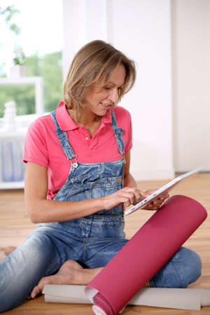 Woman sitting on the floor and choosing to wall paper color photo