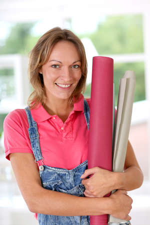 reforming: Closeup of cheerful woman holding wallpaper rolls