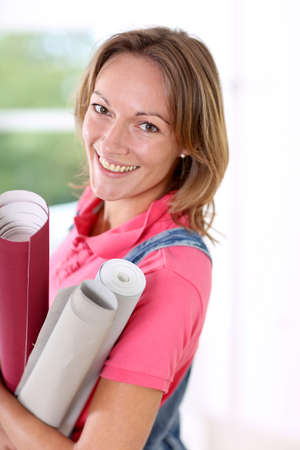 Closeup of cheerful woman holding wallpaper rolls photo
