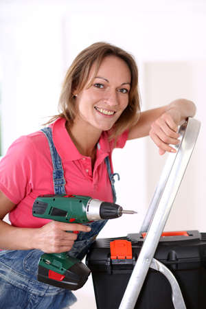 electric drill: Woman standing on scale with electric drill Stock Photo