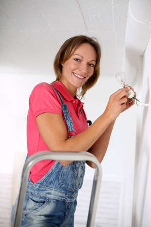 Woman standing on scale to fix light bulb Stock Photo