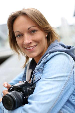amateur: Mujer que usa la cámara en la ciudad