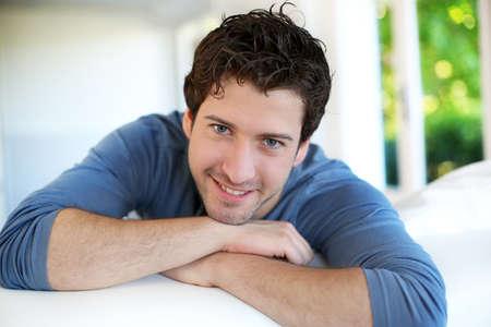 Close-up van aantrekkelijke jonge man ontspannen thuis