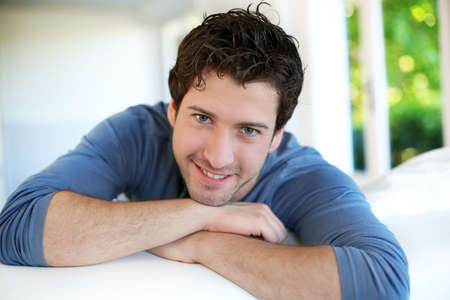 smiling young man: Closeup of attractive young man relaxing at home