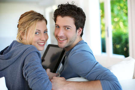 Young couple using electronic tablet photo