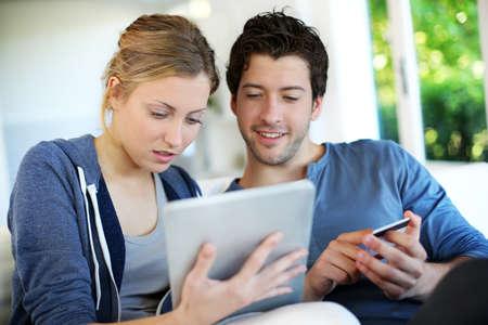 chicas comprando: Feliz pareja joven haciendo compras en internet Foto de archivo